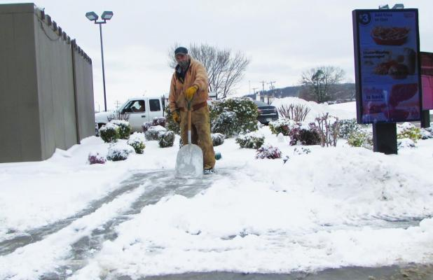 Shoveler takes a break as he clears snow and ice away from the McDonald's drive-thru.